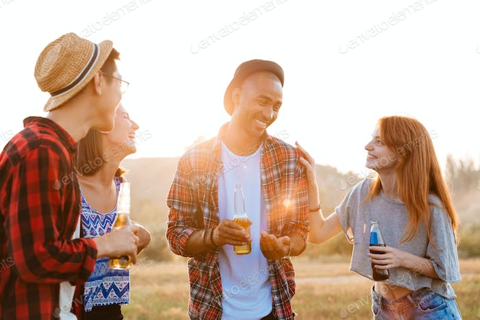 Group of smiling young friends drinking beer and soda outdoors