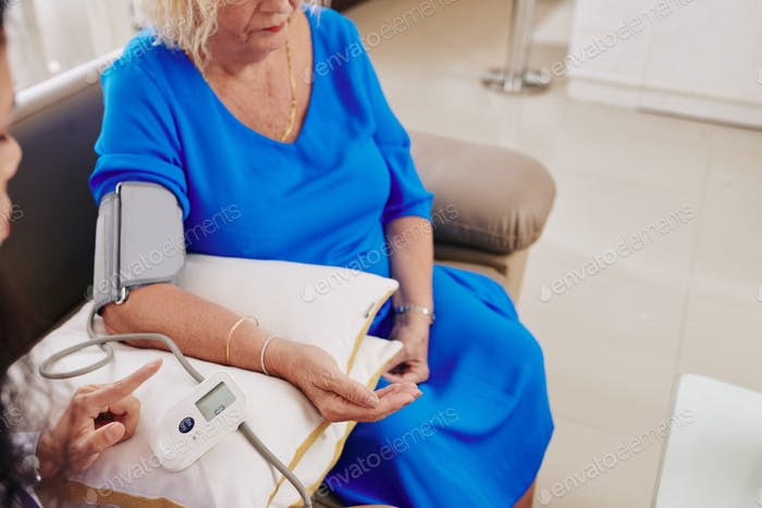 General practitioner checking blood pressure of patient