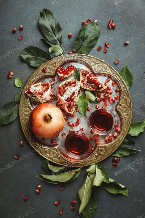 Pomegranate tea on dark background, flat lay