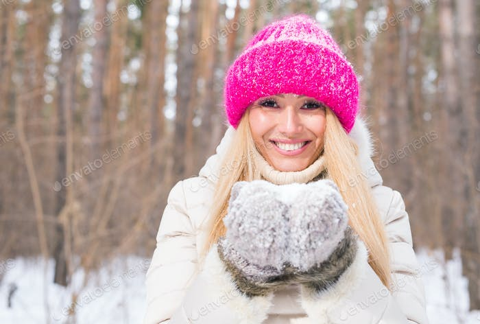 Christmas, holidays and season concept - Young beautiful smiling woman holding snow in hands in