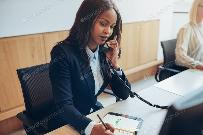 African American businesswoman taking phone messages in an office
