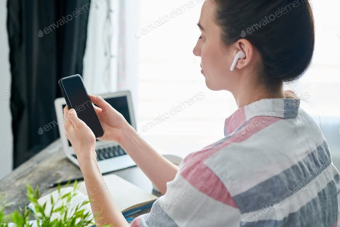 Young Woman using Smartphone at Workplace