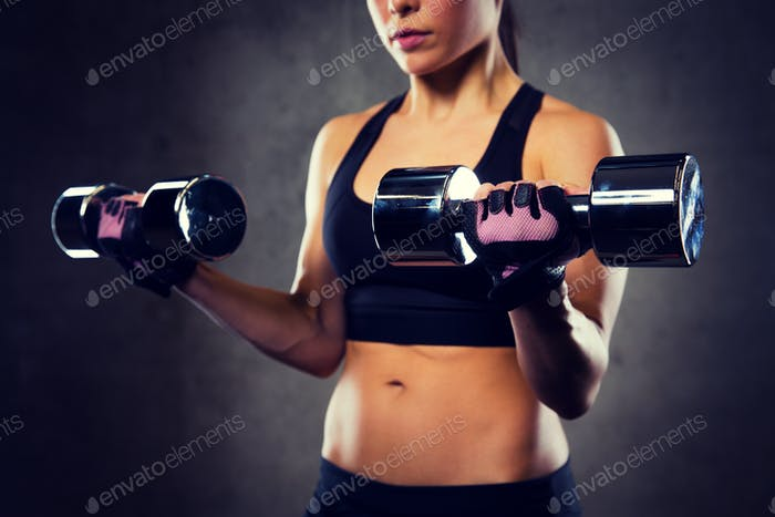 close up of woman flexing arms with dumbbells