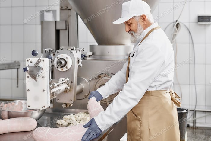 Butcher working with production of sausages at factory