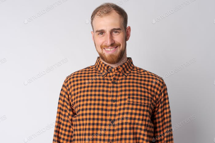 Portrait of happy young bearded hipster man smiling