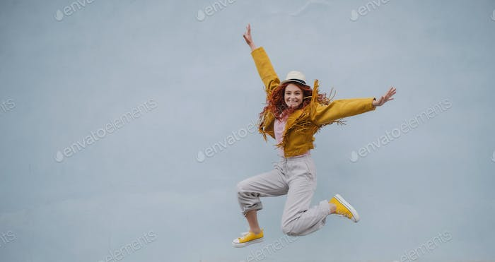 Cheerful young woman outdoors against white background, jumping