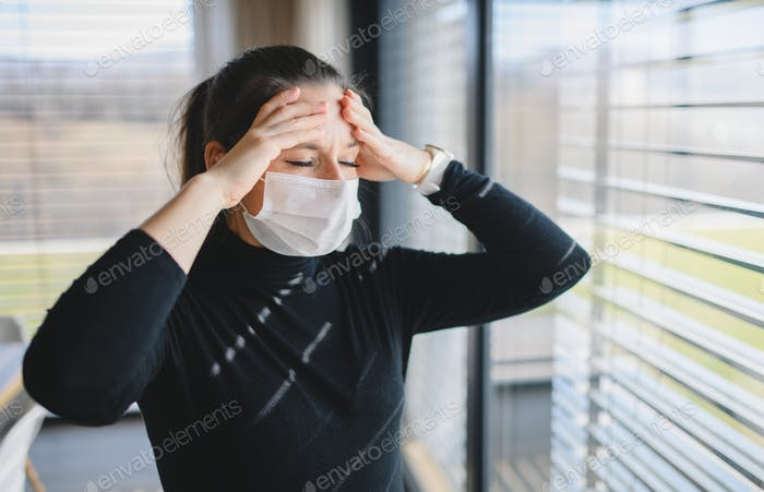 Woman with headache and face masks indoors at home, Corona virus concept
