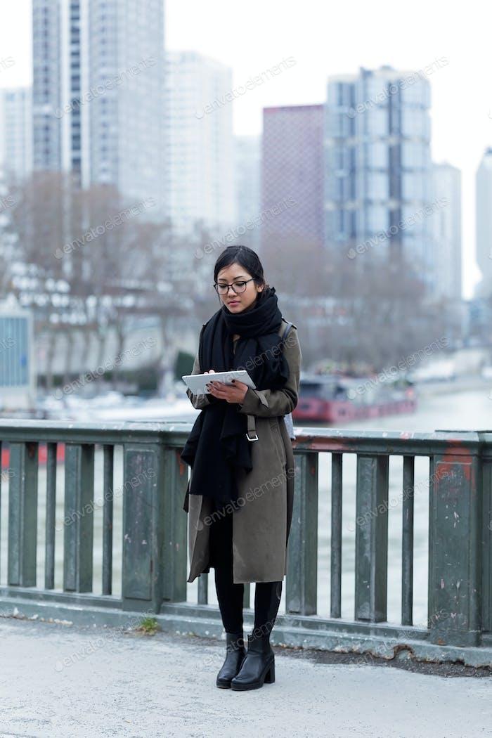 Schöne asiatische junge Frau mit ihrem digitalen Tablet vor