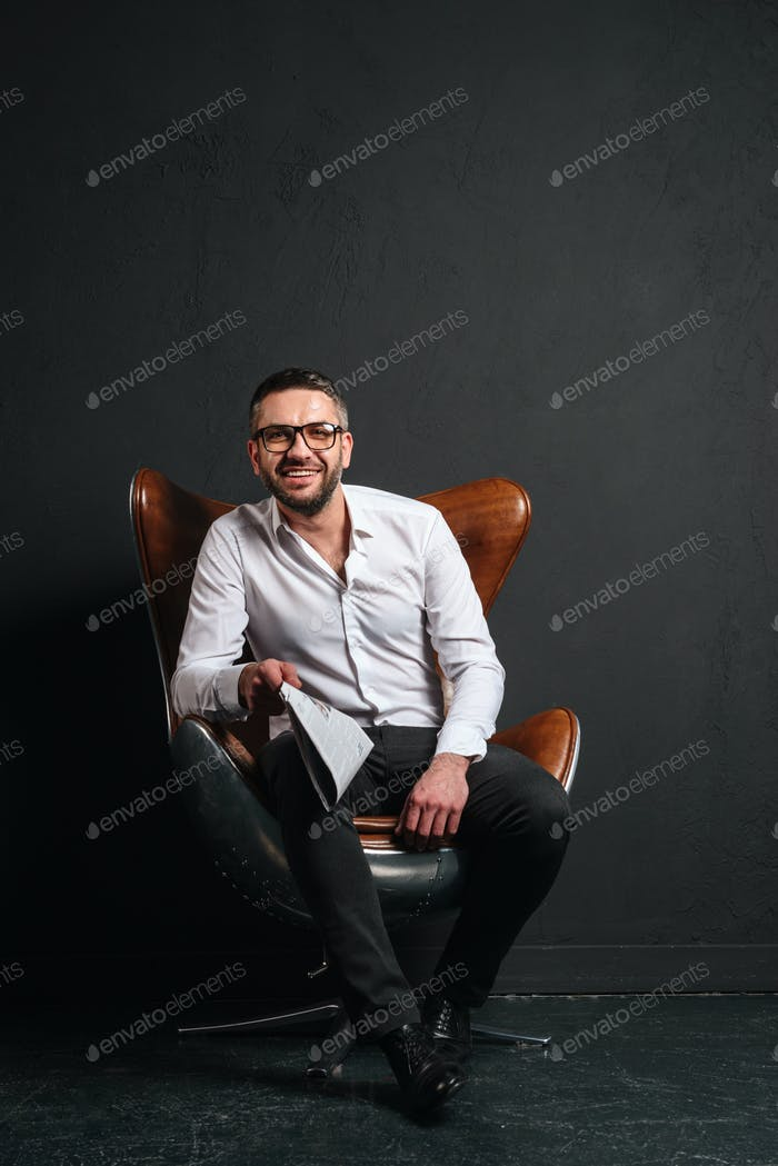 Happy businessman sitting isolated reading newspaper.