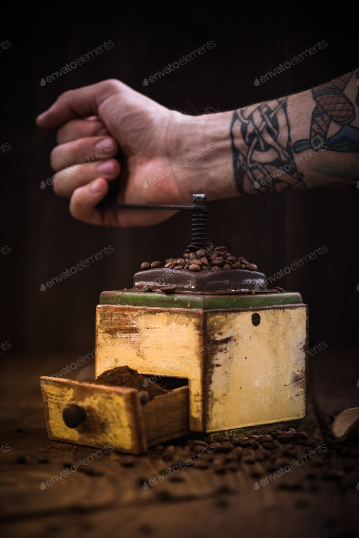 tattooed hand and coffee grinder