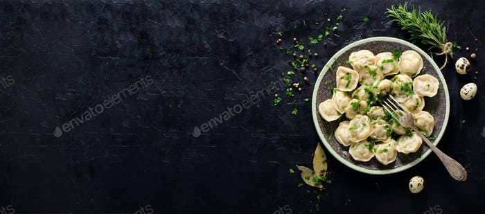 Traditional russian pelmeni, ravioli, dumplings with meat on black concrete background. Parsley