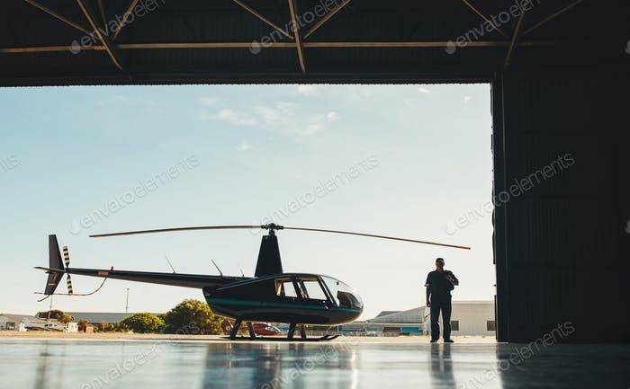 Pilot with a helicopter in airplane hangar