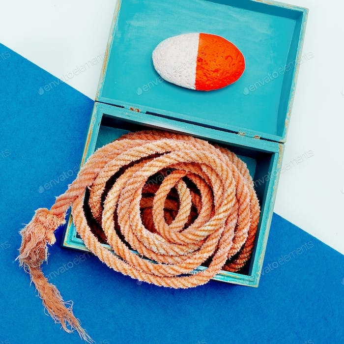 Ocean souvenirs. Sea rope and stone in the box. Minimal design a