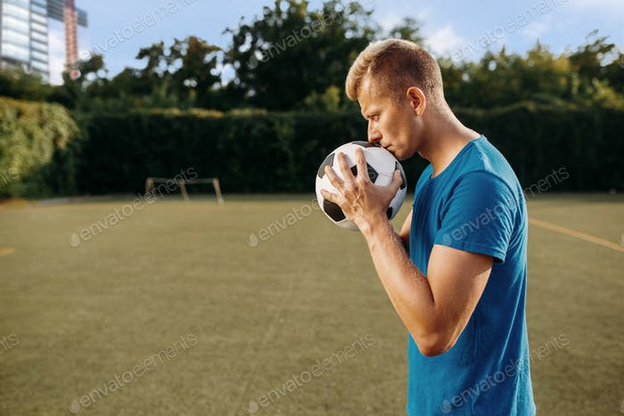 Male soccer player with ball in hands on the field
