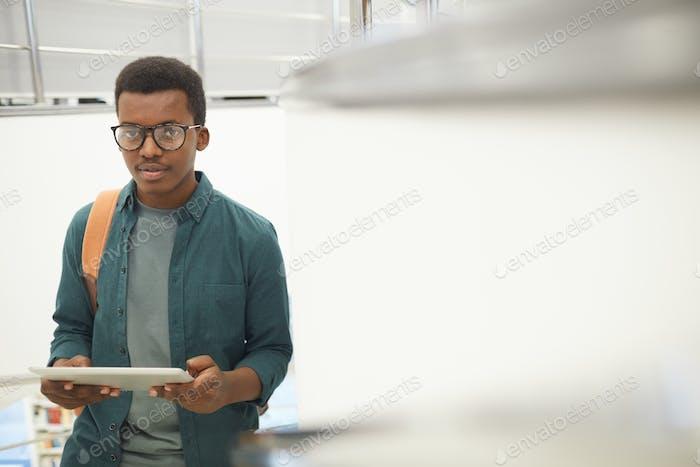 afrikanische junge Mann halten tablette in college