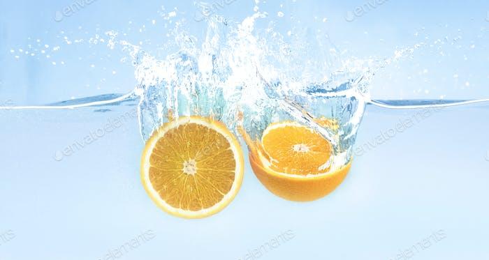 Splash of falling in water fresh orange halves
