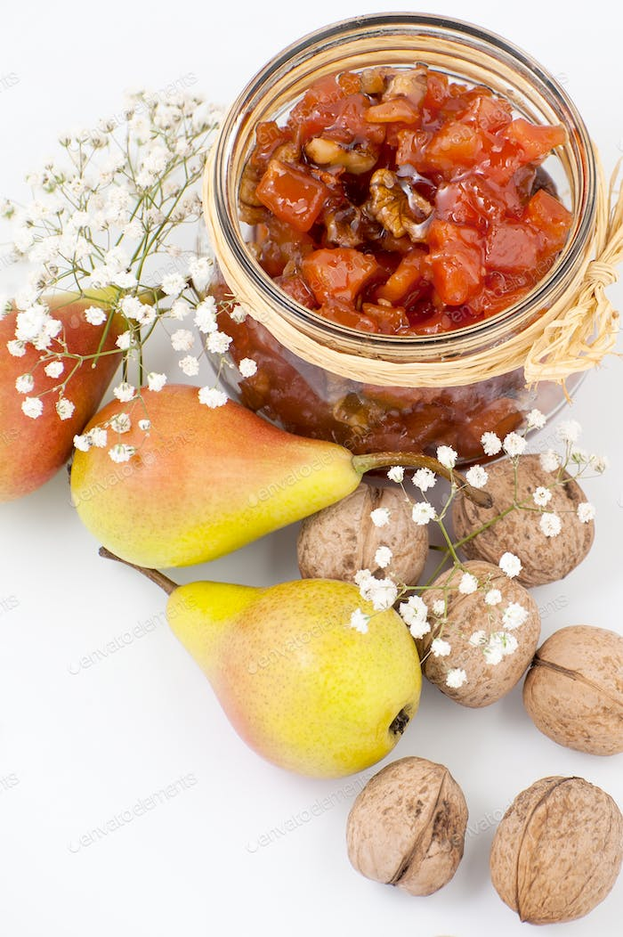 Pear jam with walnuts in a jar on a white background close-up.