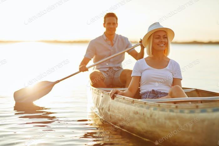 Smiling young woman canoeing on a lake with her boyfriend