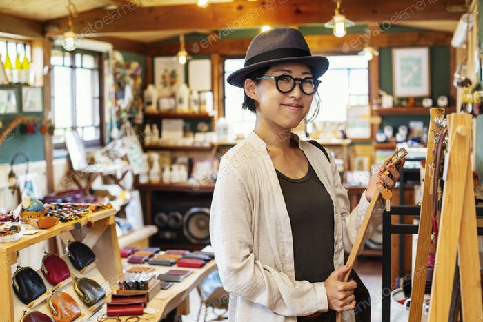 Japanese woman wearing hat and glasses standing in a leather shop, holding leather belt.