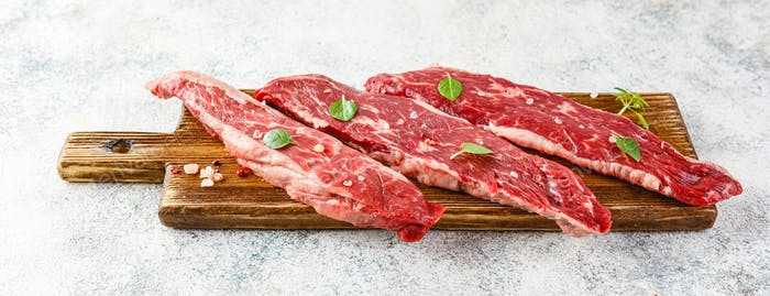 Raw steak with spices on wooden cutting board