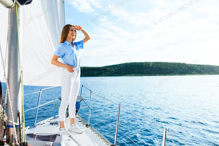 Woman Standing On Sailboat Deck Enjoying Boat Tour In Sea