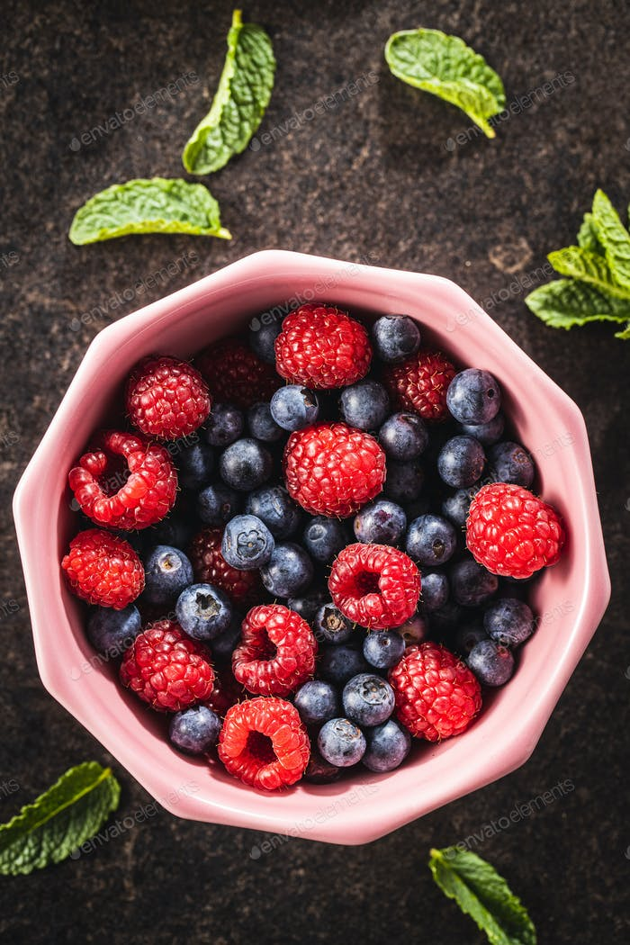 Berry fruit. Raspberries and blueberries in bowl.