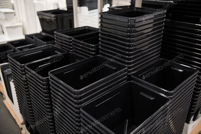 Black plastic box containers in row at store