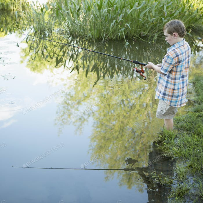 A young boy standing in water fishing with a rod.