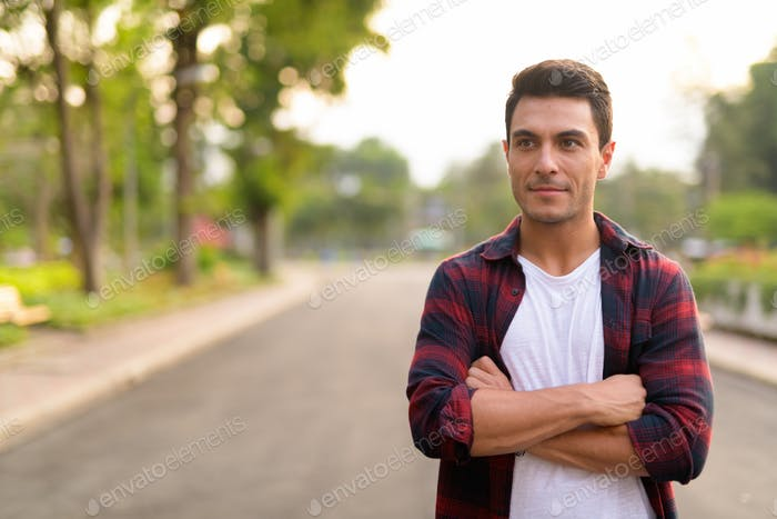 Young handsome Hispanic hipster man thinking with arms crossed at the park