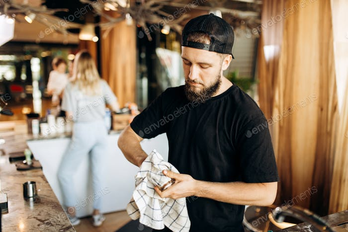 A young stylish man with beard,wearing casual clothes, wipes a glass in a modern coffee shop
