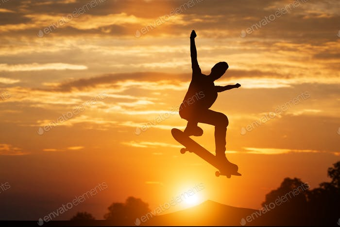 Skateboarder jumping at sunset.