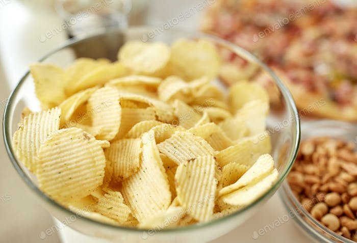 close up of crunchy potato crisps in glass bowl