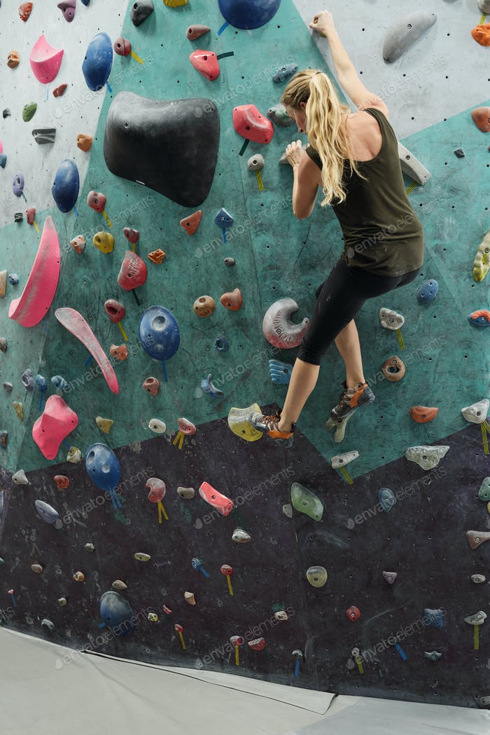 Young active female holding by artificial rocks on wall during climbing practice