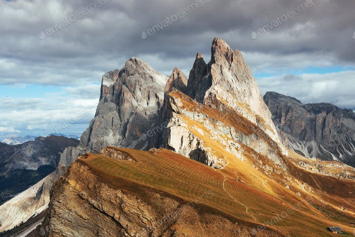 Little house standing on slope. Outstanding hills of the Seceda dolomite mountains at daytime
