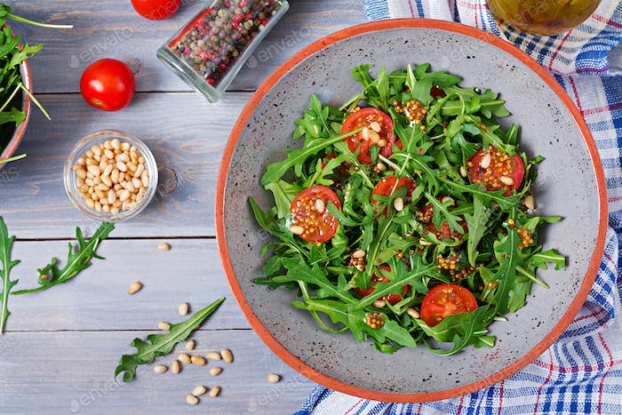 Dietary menu. Vegan cuisine. Healthy salad with arugula, tomatoes and pine nuts. Flat lay. Top view