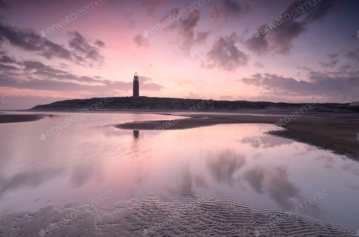 hermoso amanecer sobre la costa del mar del norte y el faro