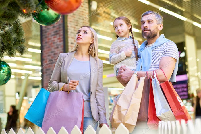 Parents with girl having Christmas shopping