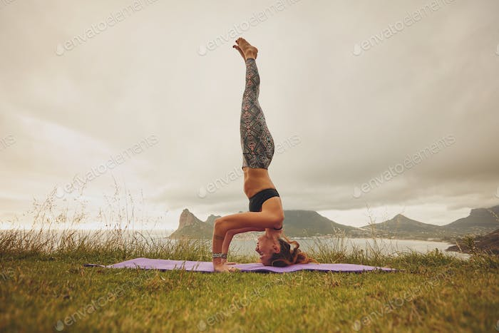 Fitness woman practicing headstand yoga outdoors