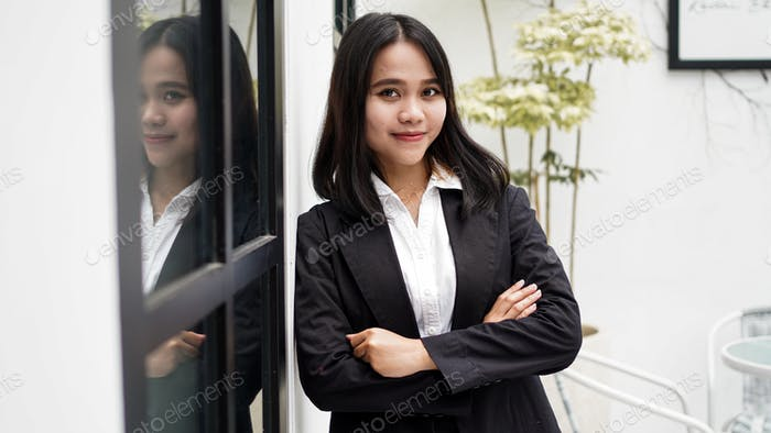 Asian business woman smiling and standing in front office