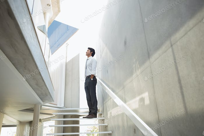 Man standing with hands in pockets on the stairs