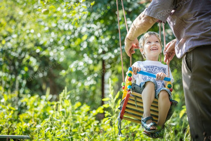 Senior man pushing happy grandson on swing