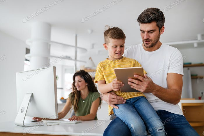 Happy family using technology devices together at home