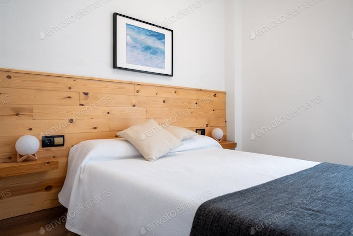 Bright white bedroom interior decorated with a photo of sea waves and a wooden headboard