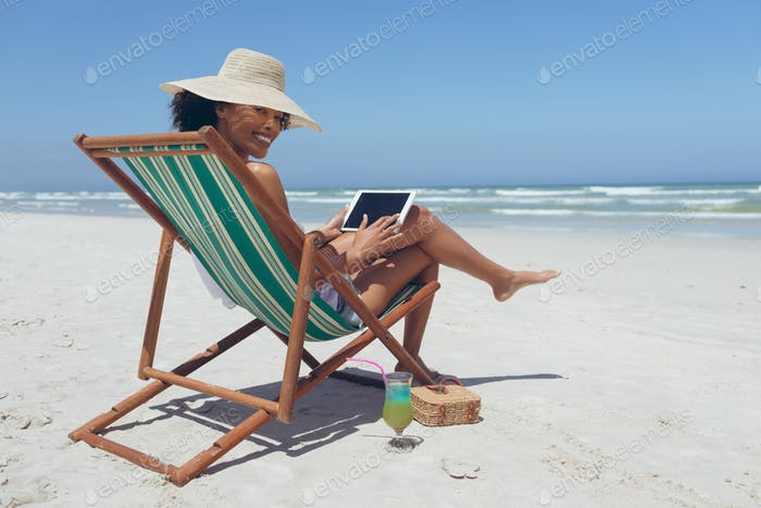 Woman using digital tablet while sitting on sun lounger at beach
