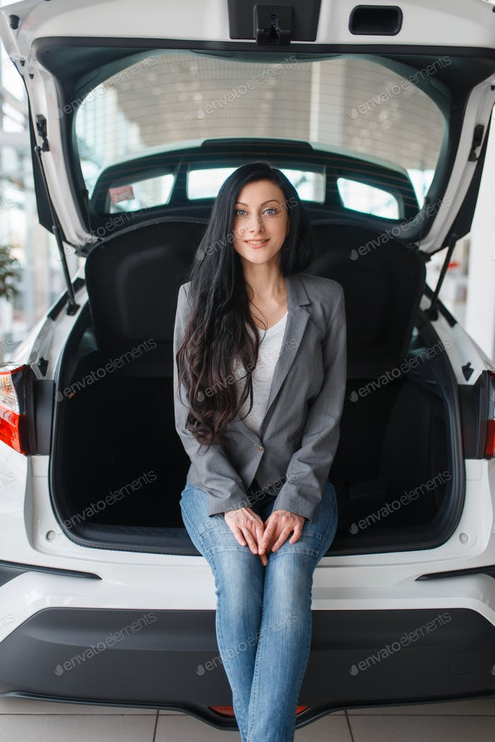 Woman buying new car, lady near the opened trunk