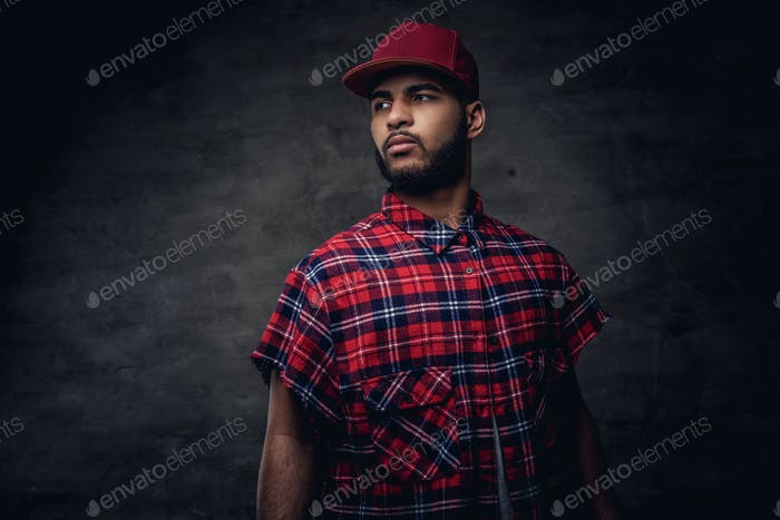 Porträt eines afroamerikanischen Hipster-Typ in einem roten Fleece-Hemd und Mütze im Studio gekleidet.