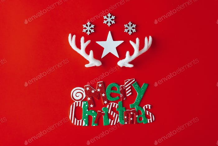 Reindeer antlers with star and snowflakes on red background. Christmas minimal Greeting card.