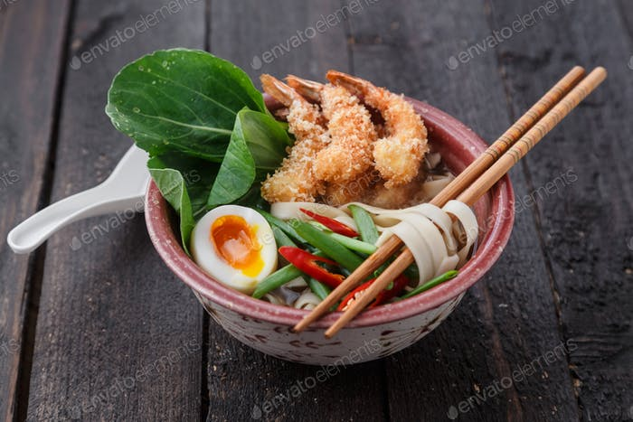 Asian spicy seafood noodle soup with tempura shrimp and greens, close view
