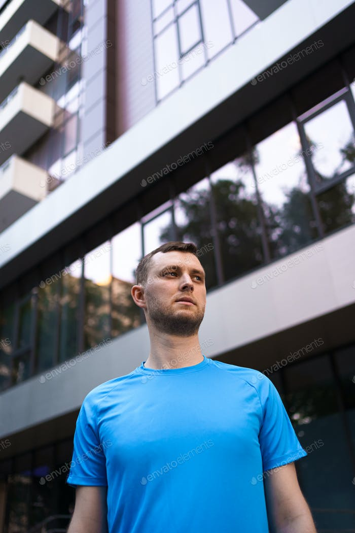 Sporty man portrait over glass building background