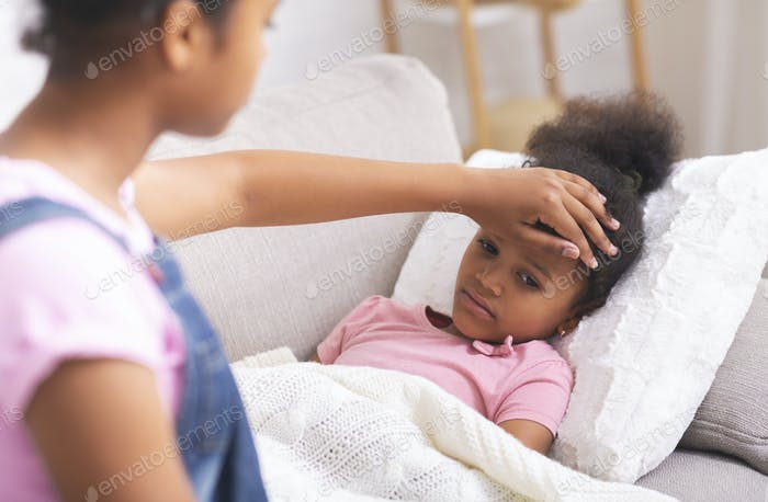 African american teen girl touching her sick little sister's forehead